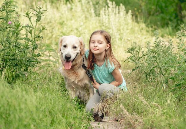 Menina com retriever dourado no prado