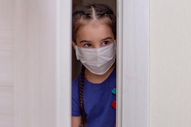 Menina com roupas azuis e máscara médica branca espia pela porta. fechar-se. copie o espaço