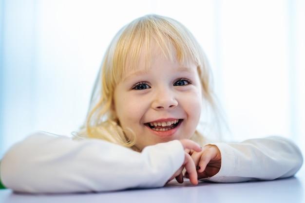 Menina com roupas brancas, olhando para a câmera e sorrindo.