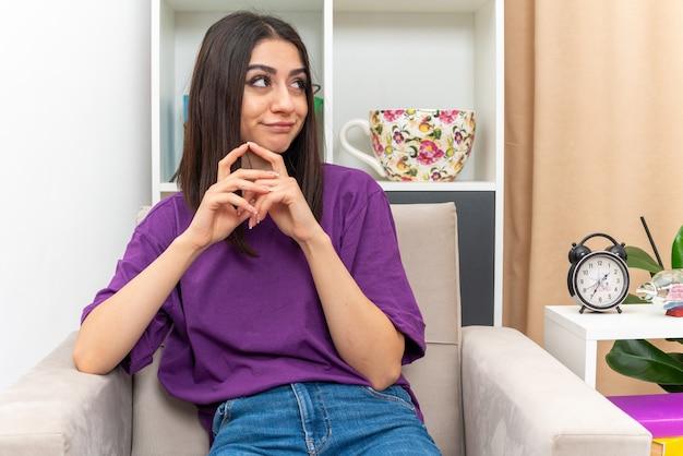 Menina com roupas casuais, olhando para o lado de mãos dadas com expressão cética, sentada em uma cadeira em uma sala iluminada