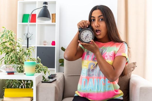 Menina com roupas casuais segurando um despertador olhando para a câmera preocupada, sentada na cadeira na sala iluminada