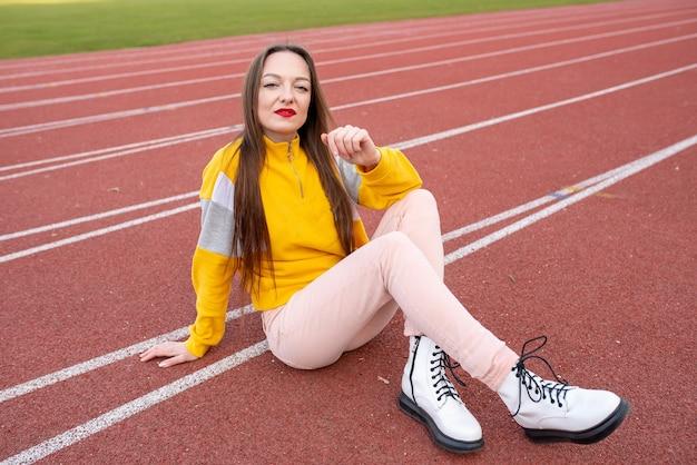 Menina, com roupas comuns, na esteira de um estádio. para qualquer propósito