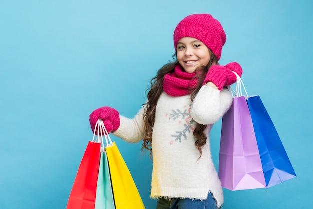 Menina com roupas de inverno e sacolas de compras