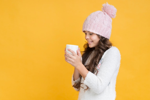 Menina com roupas de inverno e um copo nas mãos