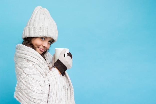 Menina com roupas de inverno e uma xícara de chá