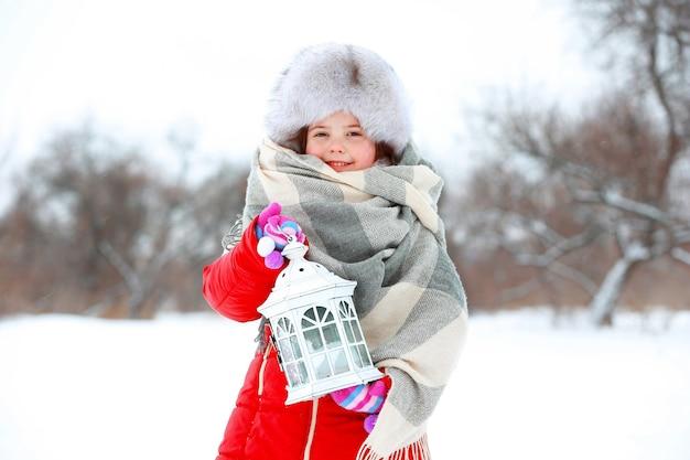Menina com roupas de inverno segurando uma lanterna branca em um parque coberto de neve ao ar livre