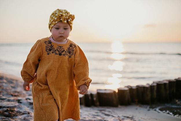 Menina com roupas orientais caminhando na praia ao pôr do sol