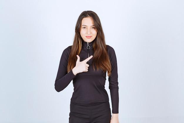 Menina com roupas pretas, apontando para algo.
