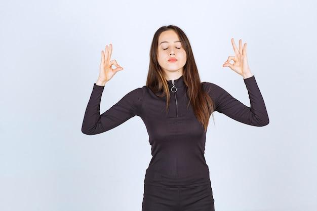 Menina com roupas pretas, fazendo meditação.