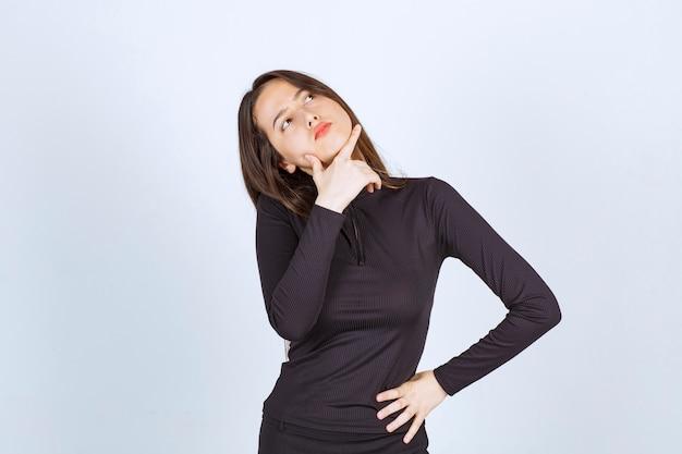 Menina com roupas pretas parece pensativa e duvidosa.