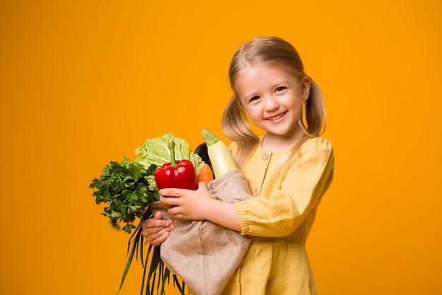 Menina com saco de eco e legumes