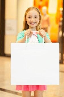 Menina com sacola de compras. menina alegre segurando sacola de compras e sorrindo para a câmera em pé no shopping