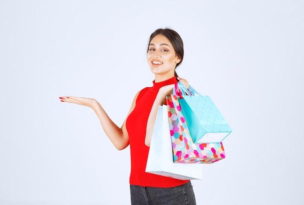 Menina com sacolas de compras coloridas, sentindo-se positiva.
