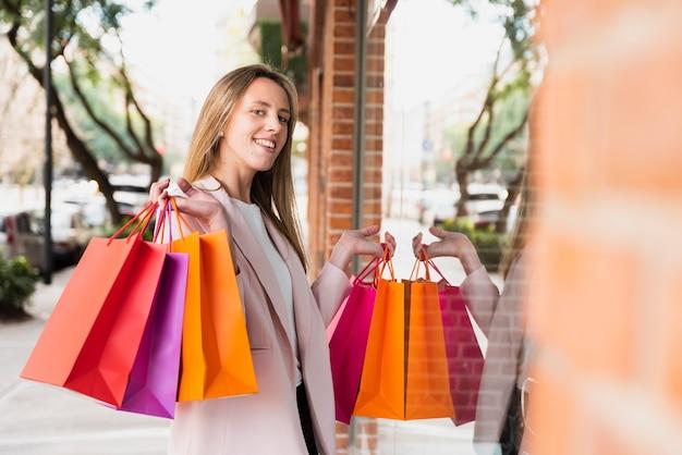 Menina com sacolas de compras em frente a janela