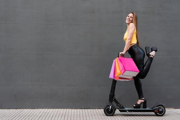 Menina com sacolas de compras em scooter elétrico