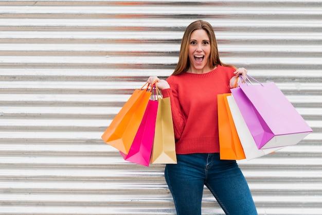 Menina com sacolas de compras, olhando para a câmera