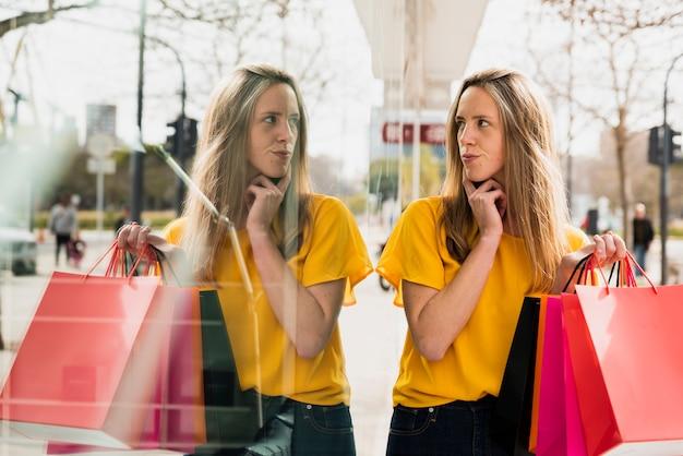 Menina com sacolas de compras, olhando para o seu reflexo