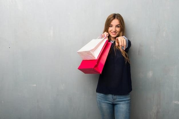 Menina com sacos de compras aponta o dedo para você com uma expressão confiante