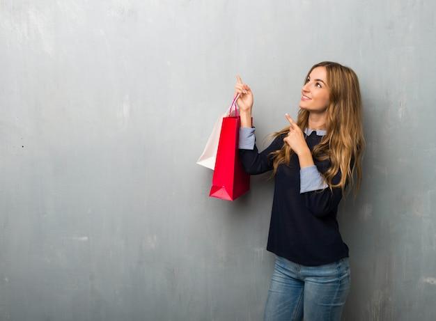 Menina com sacos de compras, apontando com o dedo indicador e olhando para cima