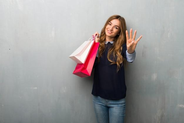 Menina com sacos de compras feliz e contando com quatro dedos