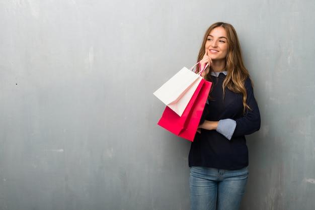 Menina com sacos de compras, olhando para o lado com a mão no queixo