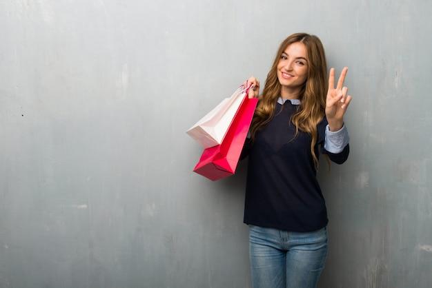 Menina com sacos de compras, sorrindo e mostrando sinal de vitória