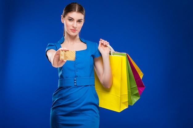 Menina com sacos e cartão de crédito nas mãos
