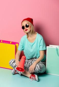 Menina com sacos e megafone perto de parede rosa