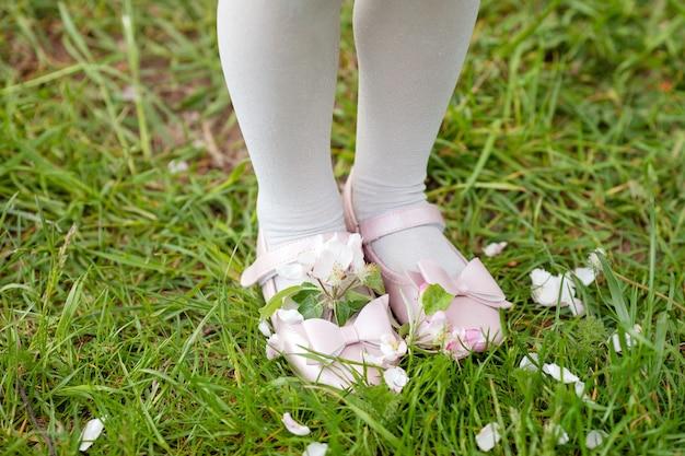 Menina com sapatos cor de rosa na grama verde do parque em flor. pés de close-up.