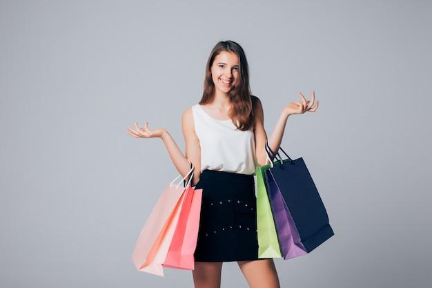 Menina com sapatos de salto alto segurando diferentes sacolas de papel, isoladas no branco