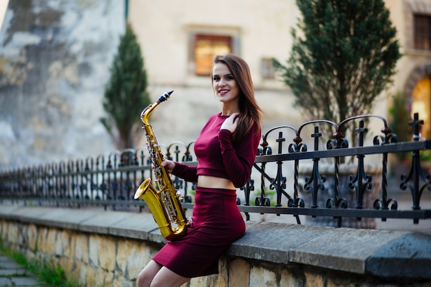 Menina com saxofone na rua