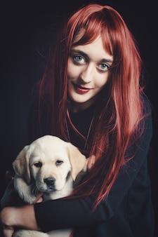 Menina com seu cachorro labrador retriever em um fundo preto