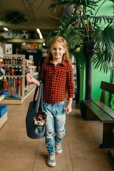 Menina com seu cachorro na bolsa, pet shop. criança comprando equipamentos em petshop, acessórios para animais domésticos
