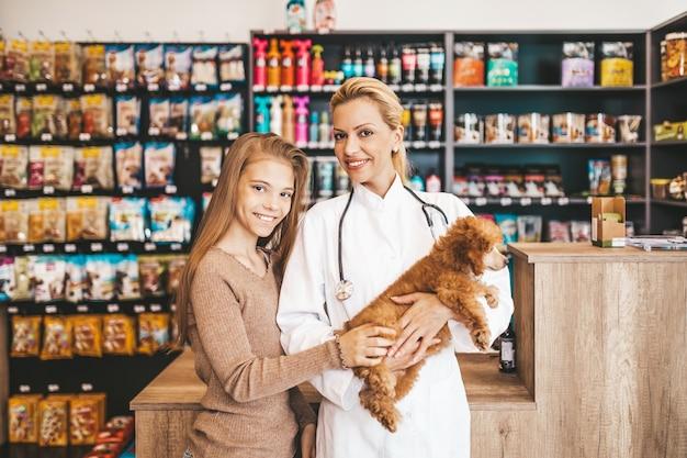 Menina com seu filhote de cachorro poodle no veterinário.