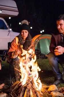 Menina com seus amigos relaxando juntos no acampamento ao redor da fogueira nas montanhas. carrinha de campista retro.
