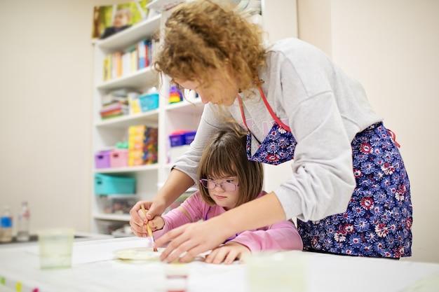 Menina com síndrome de down de óculos desenha com a ajuda de um voluntário