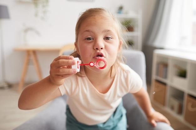 Menina com síndrome de down e soprando bolhas enquanto está sentada em casa