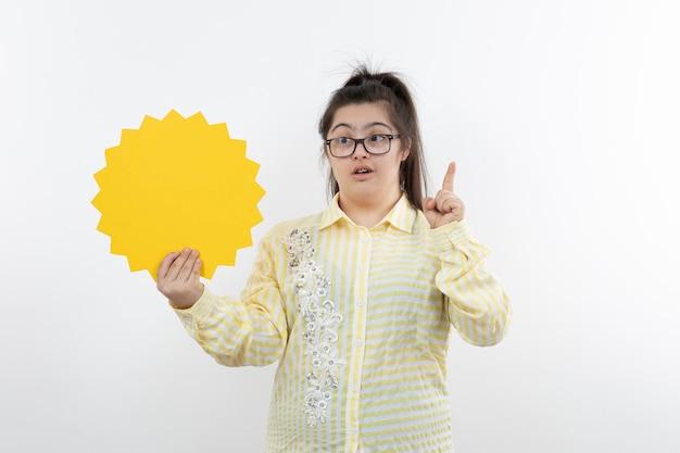 Menina com síndrome de down em óculos em pé com um balão em branco.