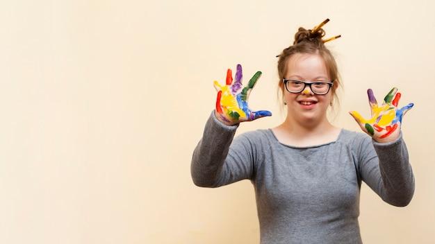 Menina com síndrome de down, mostrando as palmas das mãos coloridas