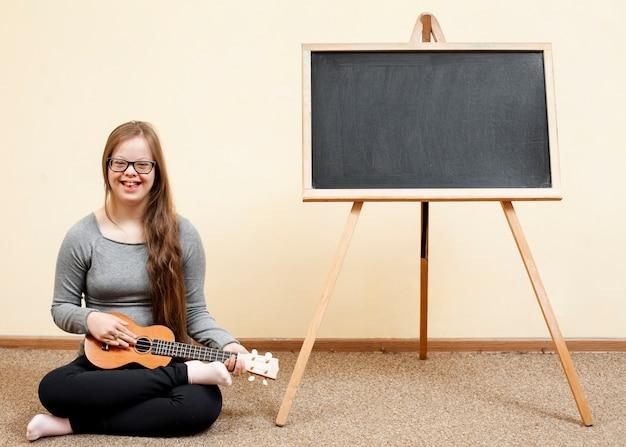 Menina com síndrome de down posando com guitarra e quadro-negro