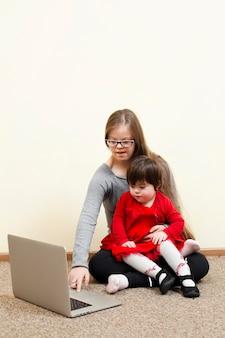 Menina com síndrome de down, segurando a criança enquanto olha para o laptop