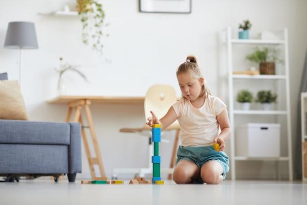 Menina com síndrome de down sentada no chão da sala construindo uma torre com blocos coloridos
