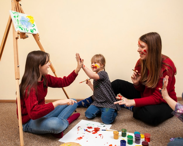 Menina com síndrome de down toca ao pintar