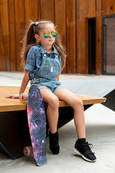 Menina com skate colorido e óculos de sol