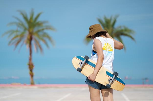 Menina com skate no braço e fundo de palmeiras