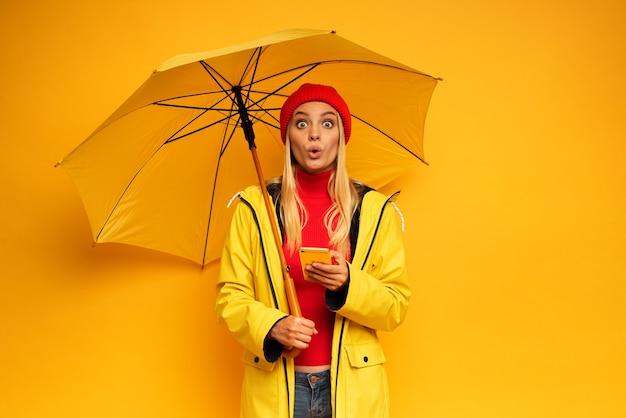 Menina com smartphone e guarda-chuva em fundo amarelo surpresa com o tempo chuvoso
