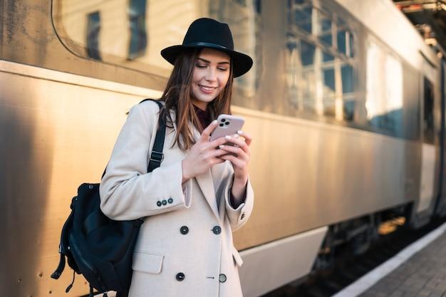 Menina com smartphone na mão na estação ferroviária.