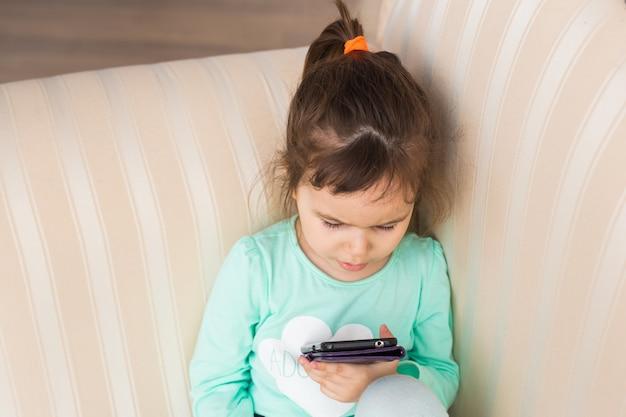 Menina com smartphone na sala