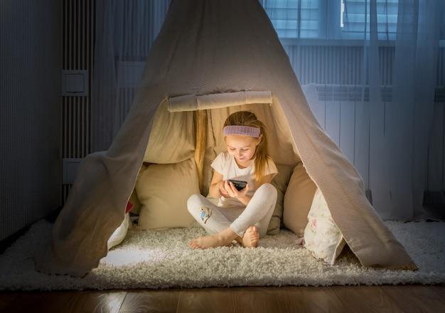 Menina com smartphone sentado na tenda