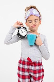 Menina com sono de pijama acaba de acordar e boceja, segurando um despertador e café em um fundo branco.